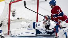 The puck sails into the net past Tampa Bay Lightning goalie Ben Bishop on a powerplay goal by Montreal Canadiens' Brian Gionta, not shown, as Canadiens's Michael Ryder looks on during third period NHL hockey action Thursday, April 18, 2013 in Montreal. (Paul Chiasson/THE CANADIAN PRESS)