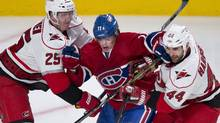 Montreal Canadiens' Brendan Gallagher gets caught in between Carolina Hurricanes' Joni Pitkanen, left, and Jay Harrison during third period NHL hockey action Monday, April 1, 2013 in Montreal. The Canadiens beat the Hurricanes 4-1. (Paul Chiasson/THE CANADIAN PRESS)