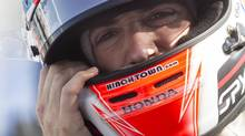 Canada's James Hinchcliffe puts on his helmet before a practice session for the Toronto Indy in Toronto on Friday, July 18, 2014. (Chris Young/THE CANADIAN PRESS)
