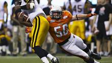 BC Lions linebacker Adam Bighill (R) reaches to get a hold of Hamilton Tiger-Cats quarterback Henry Burris during the second half of their CFL game in Vancouver, British Columbia July 6, 2012. (ANDY CLARK/REUTERS)