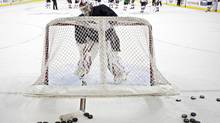 A goalie clears away some pucks in this file photo. (Jeff McIntosh For The Globe and Mail)