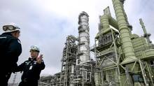 Donald Robicheaux, safety coordinator at Marathon Oil Corp.'s Garyville Refinery, right, speaks near the recently completed crude oil unit at the refinery in Garyville, Louisiana, U.S., on Thursday, March 25, 2010. (Patrick Semansky/Bloomberg)