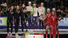 Winning team Netherlands, centre, team Canada, second place, and team Poland, third place, pose after the women's team pursuit at the World Single Distances Speed Skating Championships at Thialf stadium in Heerenveen, Netherlands, Sunday. (Peter Dejong/AP 2012)
