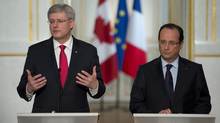 Canadian Prime Minister Stephen Harper, left, responds to a question as French President Francois Hollande looks on during a joint news conference at the Palais de l'Elysee on Friday, June 14, 2013 in Paris, France. (Adrian Wyld/CP)