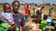 Tobias Gumboreshumba, holding his daughter as he waits with other residents in a queue for water at a borehole near his home in Mabvuku, a poor suburb near Harare.