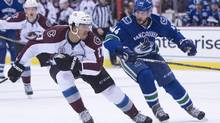 Colorado Avalanche center Andreas Martinsen fights for control of the puck with Vancouver Canucks defenceman Matt Bartkowski during first period NHL action in Vancouver, B.C. Wednesday, March 16, 2016. (JONATHAN HAYWARD/THE CANADIAN PRESS)