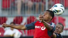 Toronto FC forward Ryan Johnson heads the ball past a CD Aguila defender during first half CONCACAF soccer action in Toronto on August 1. (Nathan Denette/Canadian Press)