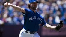 Toronto Blue Jays starting pitcher R.A. Dickey throws out Baltimore Orioles outfielder Adam Jones at first base during third inning AL action in Toronto on Saturday, May 25, 2013. (Frank Gunn/The Canadian Press)