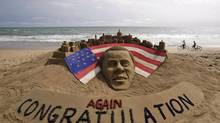 Cyclists ride on a beach passing by a sand sculpture congratulating U.S. president Barack Obama for a second term in office in Puri, India, Wednesday, Nov. 7, 2012. (BISWARANJAN ROUT/AP)