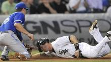 The Chicago White Sox' Gordon Beckham is tagged out by Toronto Blue Jays third baseman Mark DeRosa in Chicago Tuesday night. (PAUL BEATY/AP)