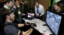 Another trend we've seen develop over the last year is sure to get a lot of floor space: AR and VR gaming rigs. Here, YEI Technology's Chris George plays a computer game with PrioVR, a virtual reality gaming accessory in which sensors on the player translate movement into the game (and possibly gives him Elysium-like robot super powers?). A full-body system retails for $400. (STEVE MARCUS/REUTERS)