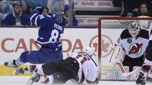 Toronto Maple Leafs' Phil Kessel is hauled down by New Jersey Devils' Stephen Gionta as he scores on goalie Cory Schneider during third period NHL action in Toronto on Nov. 8, 2013. (FRANK GUNN/THE CANADIAN PRESS)