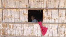 A woman looks through a window in her house in the Rovieng District of Preah Vihear province, Cambodia, Feb. 10, 2013. The remote district boasts iron ore deposits – supposedly in such huge quantities two Chinese companies have an $11-billion plan to extract it. (SAMRANG PRING/Reuters)