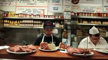 Para, left, and Pierre prepare smoked meat sandwiches at Schwartz's deli on St. Laurent in Montreal, Feb. 5, 2012. (Christinne Muschi/Reuters)