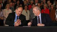 BC NDP leader John Horgan looks on as B.C. Green party leader Andrew Weaver checks the time before signing an agreement on creating a stable minority government during a press conference in the Hall of Honour at Legislature in Victoria, B.C. (CHAD HIPOLITO/THE CANADIAN PRESS)