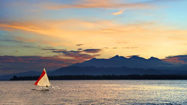 Local outrigger sailing boat sailing past a volcano island in a tropical sea during sunrise, Gili Travangan island, Indonesia.