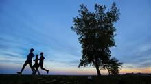 Joggers run along the shores of Lake Ontario as the sun sets in Toronto. (Kevin Van Paassen/The Globe and Mail)