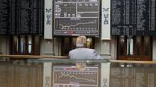 A trader looks at electronic boards, which are reflected on a table, at the stock exchange in Madrid July 6, 2012. (ANDREA COMAS/REUTERS)