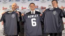 Eric Perez, the founder and CEO of the Toronto Wolfpack, left, head coach Paul Rowley and Toronto Mayor John Tory hold up jerseys of the new rugby league team on April 27, 2016. (Neil Davidson/The Canadian Press)