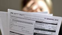 A taxpayer examines income-tax forms in Toronto on April 13, 2011. (Chris Young/The Canadian Press/Chris Young/The Canadian Press)