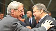 Eurogroup president Jean-Claude Juncker offers his arm to Greek Finance Minister Evangelos Venizelos at the EU headquarters in Brussels on Monday. (Georges Gobet/AFP/Getty Images)