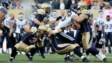 Toronto Argonauts' quarterback Mitchell Gale is sacked by Winnipeg Blue Bombers' Greg Peach and Zach Anderson (Trevor Hagan/THE CANADIAN PRESS)