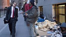 Occupy Wall Street protester Yoni Miller, right, hands out flyers to people at the corner of Wall Street and Nassau Street, across the street from the New York Stock Exchange. (ANDREW BURTON/REUTERS)