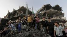 Palestinians attend a victory rally organized by masked militant of Izzedine al-Qassam Brigades, military wing of Hamas, at the debris of destroyed houses in Shijaiyah, neighborhood of Gaza City, in the northern Gaza Strip. (Adel Hana/AP)