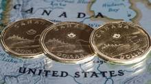 Canadian dollar coins, or Loonies, are displayed on a map of North America on January 9, 2014 in Montreal. (PAUL CHIASSON/THE CANADIAN PRESS)