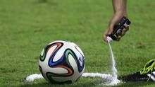 FILE - In this June 6, 2014, file photo, a referee uses vanishing spray during a referee's training session in Rio de Janeiro, Brazil. English Premier League referees will start using a vanishing spray to prevent encroachment by players in a defensive wall during free kicks. (Hassan Ammar/AP)