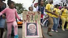 "A young girl with a placard showing the face of Nelson Mandela and referring to his clan name ""Madiba"", marches with others to celebrate his life, in the street outside his old house in Soweto, Johannesburg, South Africa, Friday, Dec. 6, 2013."