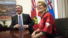 Ontario Premier Kathleen Wynne, right, wears a Calgary Stampeders jersey while meeting with Alberta Premier Jim Prentice following a friendly bet on the Grey Cup at Queen's Park in Toronto on Wednesday, December 3, 2014. (Darren Calabrese/THE CANADIAN PRESS)