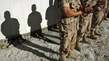 The shadows of Canadian troops are cast on a memorial for fallen soldiers as they applaud a speech by Defence Minister Peter MacKay at Kandahar Air Field on November 5, 2007. (FINBARR O'REILLY/REUTERS)