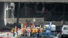 Engineers inspect a concrete slab that fell on a major expressway Aug. 1, 2011 in Montreal. (Paul Chiasson/THE CANADIAN PRESS)