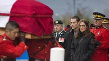Pallbearers carry the casket of RCMP constable Adrian Oliver past family members during a regimental funeral in Langley, B.C., on Tuesday, November 20, 2012. (John Lehmann/The Globe and Mail)