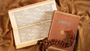 Rigved in sanskrit book explaining Indian Vedas with rudraksha mala on satin cloth.