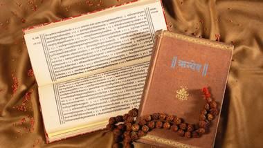 Rigved in sanskrit book explaining Indian Vedas with rudraksha mala on satin cloth.