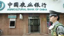 A security guard walks past a branch of the Agricultural Bank of China. (FREDERIC BROWN/AFP PHOTO/Frederic J. BROWN)