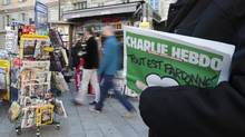 A man holds the latest issue of satirical French weekly Charlie Hebdo in Nice, France, on Wednesday. The country has been caught up this week in shows of support for free speech, while a popular entertainer's controversial shows have been banned. (ERIC GAILLARD/Reuters)