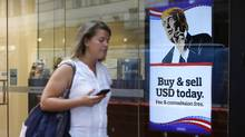 A woman walks past an advertisement featuring a cartoon of U.S. President-elect Donald Trump at a currency exchange store in the central business district in Sydney, Australia, on Thursday, Nov. 10, 2016. (David Moir/Bloomberg)