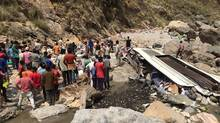 Indian rescue personnel and volunteers stand amidst wreckage and victims after a bus accident, at the bottom of a ravine near the River Tons at Chopal, April 19, 2017. (STR/AFP/Getty Images)