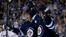 Winnipeg Jets' Mark Scheifele (55) and Michael Frolik (67) celebrate after Frolik opened the scoring goal against the Edmonton Oilers during second period preseason NHL action in Winnipeg, Tuesday, September 17, 2013. (Trevor Hagan/THE CANADIAN PRESS)