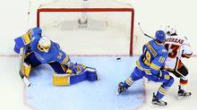 A shot by Calgary Flames defenceman Matt Bartkowski goes in off the left skate of St. Louis Blues defenceman Jay Bouwmeester past goaltender Jake Allen to tie the game in the third period of an NHL hockey game Saturday, March 25, 2017, at the Scottrade Center in St. Louis. (Chris Lee/AP)