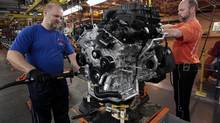 Chrysler auto worker Keith Sinclair, left, works on assembling the engine for the new 2011 Dodge Grand Caravan's and Chrysler Town & Country minivans at the Windsor Assembly Plant in Windsor, Ontario January 18, 2011. Chrysler Group Chief Executive Sergio Marchionne vowed to keep the automaker on top of the minivan segment in the North American market and said the company will develop a new type of minivan by 2014. (REBECCA COOK/Reuters)