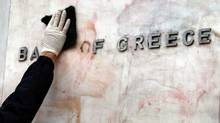 A worker cleans the sign of the Bank of Greece from red and black paint, after Sunday's riots, in Athens, on Tuesday, Feb. 14, 2012. (Thanassis Stavrakis/Thanassis Stavrakis/AP)