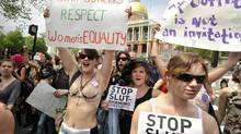 Women march past the Statehouse during the SlutWalk in Boston, Saturday, May 7, 2011, a demonstration against those who blame the victims of sex crimes. (JOSH REYNOLDS/AP)