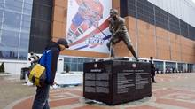 In this file photo, A fan reads the inscription under the statue of Montreal Canadiens great Jean Beliveau outside the Bell Center in Montreal Thursday, Jan. 22, 2009. The NHL club announced a new 12-year broadcasting rights deal and naming rights deal on Friday. (RYAN REMIORZ/The CANADIAN PRESS)