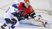 Calgary Flames goalie Reto Berra (29) makes a save as St. Louis Blues center Derek Roy (12) tries to score during the shootout at Scotiabank Saddledome. Calgary Flames won 4-3. (SERGEI BELSKI/USA TODAY SPORTS)