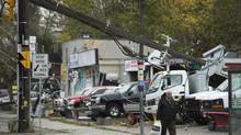 A man walks past damaged power lines in Toronto on Tuesday, Oct. 30, 2012 as power lines were down after superstorm Sandy hit the city late Monday night causing power outages. (Nathan Denette/THE CANADIAN PRESS)
