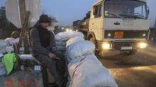 A member of a local self-defense unit mans a checkpoint on the highway between Kherson and Simferopol in the town of Tsyurupinsk, Ukraine's region adjacent to Crimea, March 13, 2014. (VALENTYN OGIRENKO/REUTERS)